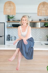 Hayley Stathis Business & Marketing Coach for Nutritionists and Health Coaches sitting on a kitchen counter