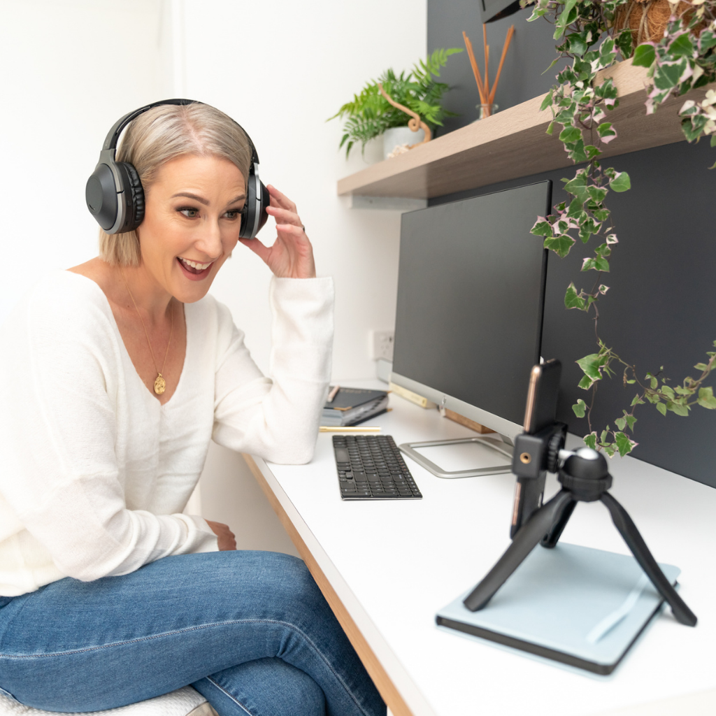 Hayley Stathis, Business & Marketing Coach for Health & Wellness Practitioners, sitting at her desk coaching clients online with her iphone and headphones